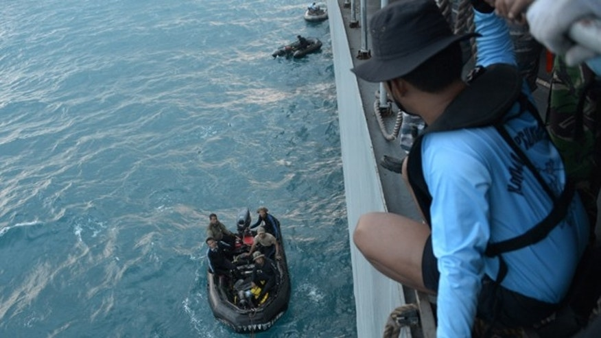 Jan. 9, 2015: Indonesian navy divers prepare operations to lift the tail of AirAsia Flight 8501 in the Java Sea. (AP Photo/Adek Berry, Pool)
