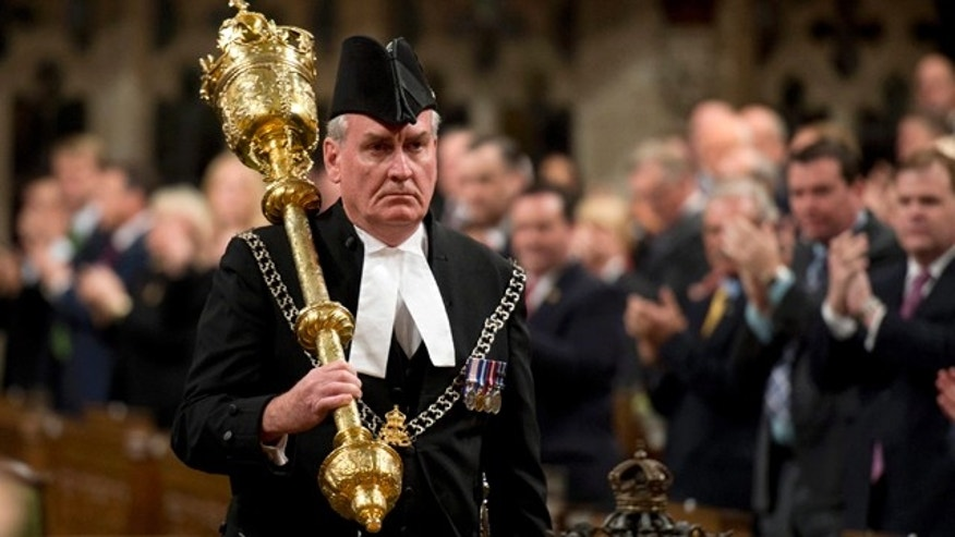 Oct. 23, 2014: Sergeant-at-Arms Kevin Vickers receives a standing ovation as he enters the House of Commons in Ottawa. (AP Photo/The Canadian Press, Adrian Wyld, File)