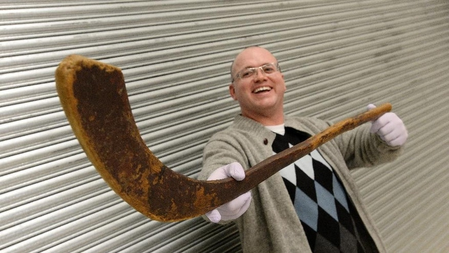Mark Presley holds what is believed to be the world's oldest known ice hockey stick during an announcement at the Canadian Museum of History in Ottawa on Wednesday, Jan. 9, 2015. (AP Photo/The Canadian Press, Sean Kilpatrick)