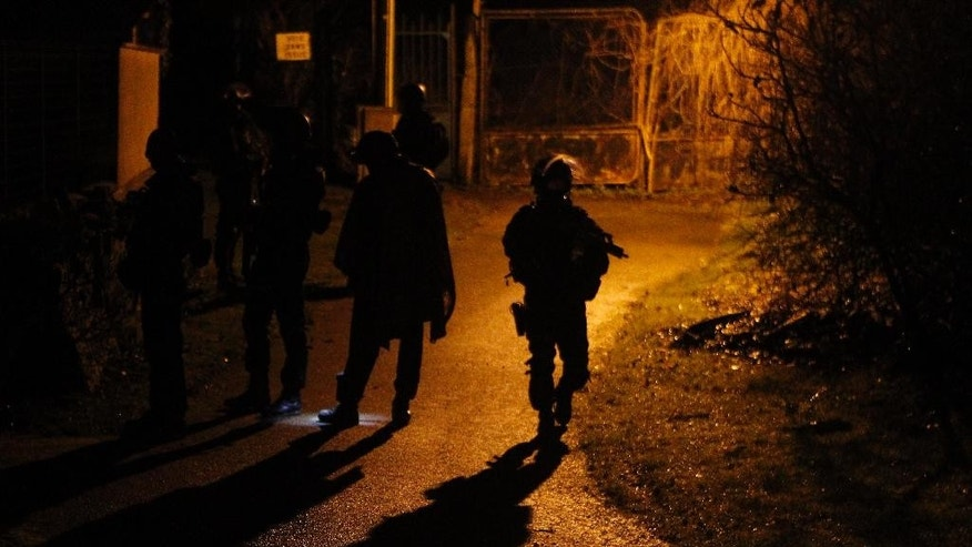 Armed police officers patrol in the village of Fleury, north east of Paris, hunting down the two heavily armed brothers suspected in Wednesday's massacre at Charlie Hebdo newspaper, Thursday, Jan. 8, 2015. Scattered gunfire and explosions shook France on Thursday as its frightened yet defiant citizens held a day of mourning for 12 people slain at a Paris newspaper. (AP Photo/Michel Spingler)