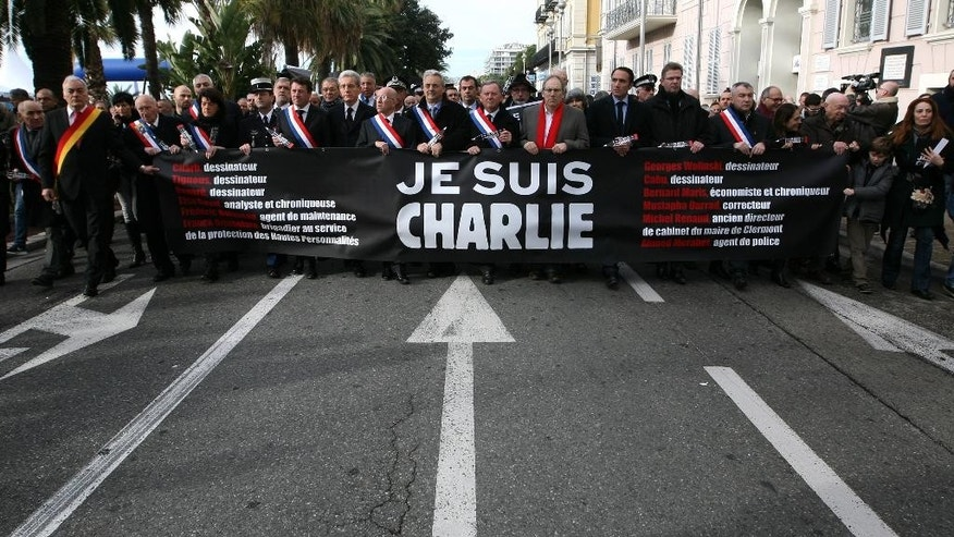 "People holding a banner reading ""I am Charlie"", take part to silent walk for victims of the shooting at the satirical newspaper Charlie Hebdo, Saturday, Jan. 10, 2015, in Nice, southeastern France. Ten journalists and two policemen were killed last Jan. 07 in a terrorist attack at the Charlie Hebdo headquarters in Paris. (AP Photo/Lionel Cironneau)"