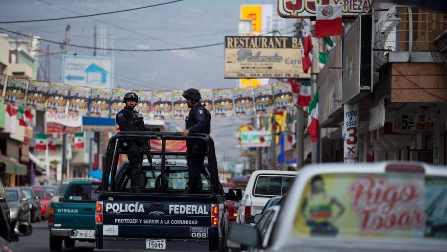 Federal police patrol in Apatzingan in Michoacan state, Mexico, Thursday, Jan. 8, 2015. Confrontations in Apatzingan began Tuesday when federal forces moved in to take control of city hall, which had been held for days by civilians whose demands and identities were unclear, according to Michoacan state Commissioner Alfredo Castillo. The second clash came when gunmen attacked soldiers who were transporting the seized vehicles to an impound lot, Castillo said. However, family members and witnesses tell a different story, one with a higher death toll. (AP Photo/Rebecca Blackwell)