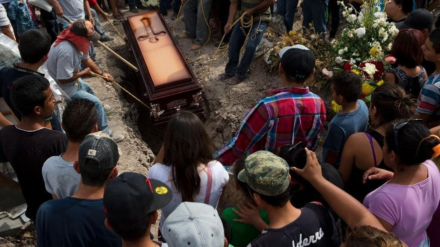 Mourners lower the coffin of shooting victim in Apatzingan, Michoacan state, Mexico, Thursday, Jan. 8, 2015. Confrontations in Apatzingan began Tuesday when federal forces moved in to take control of city hall, which had been held for days by civilians whose demands and identities were unclear, according to Michoacan state Commissioner Alfredo Castillo. The second clash came when gunmen attacked soldiers who were transporting the seized vehicles to an impound lot, Castillo said. However, family members and witnesses tell a different story, one with a higher death toll. (AP Photo/Rebecca Blackwell)