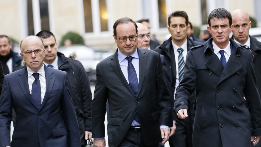 Jan. 9, 2015: French President Francois Hollande, center, leaves the Interior Ministry following a meeting with prime minister Manuel Valls, right, and interior minister Bernard Cazeneuve, left, in Paris.