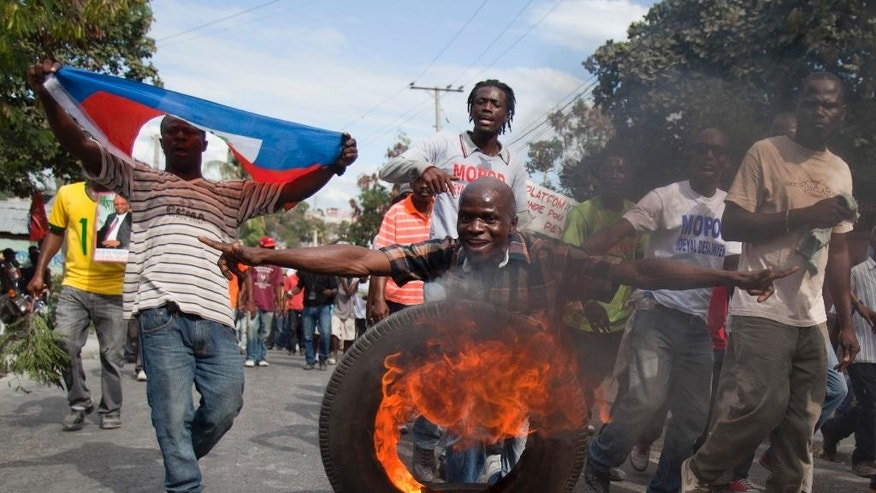 Protesters march through the streets of Port-au-Prince, Haiti, Saturday, Jan. 10, 2015, during a protest calling for the resignation of President Michel Martelly, a former pop star who took office in May 2011. He has been embroiled in a stalemate with lawmakers over parliamentary elections, delayed for over three years. (AP Photo/Dieu Nalio Chery)