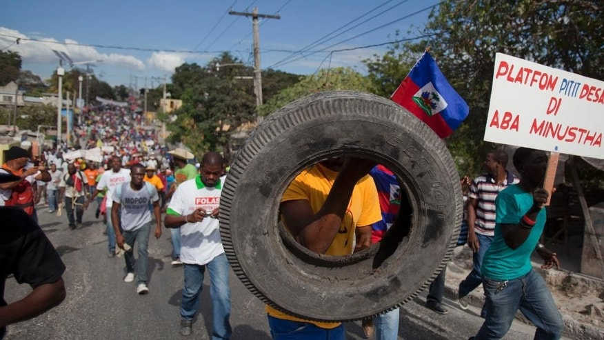 Protesters march through the streets of Port-au-Prince, Haiti, Saturday, Jan. 10, 2015, during a protest calling for the resignation of President Michel Martelly, who took office in May 2011. Recovery from the the Jan. 12, 2010, 7.0 earthquake has been uneven, plagued by poor planning and accusations of graft. Many poor Haitians say their lives have been complicated by a rising cost of living and lack of jobs, and they put the blame squarely on the government for failing to create opportunities. (AP Photo/Dieu Nalio Chery)