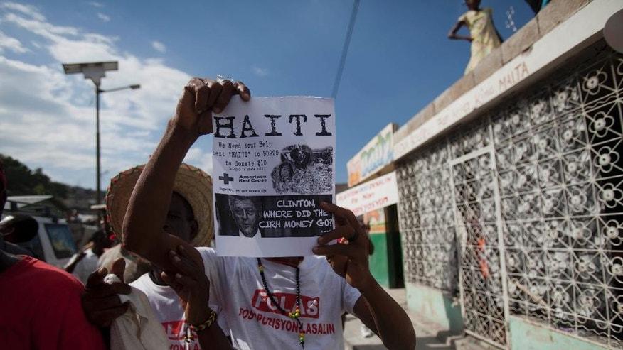 A demonstrator holds up a leaflet that shows an image of former president Bill Clinton, asking where the aid money for reconstruction went, in Port-au-Prince, Haiti, Saturday, Jan. 10, 2015, during a protest calling for the resignation of Haiti's President Michel Martelly. Recovery from the the Jan. 12 2010, 7.0 earthquake has been uneven, plagued by poor planning and accusations of graft. Many poor Haitians say their lives have been complicated by a rising cost of living and lack of jobs, and they put the blame squarely on the government for failing to create opportunities. ( AP Photo/Dieu Nalio Chery)
