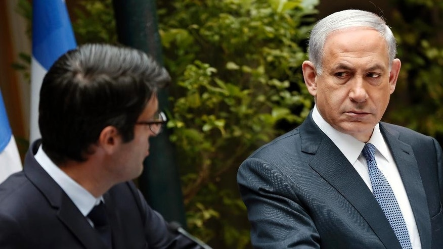 Israeli Prime minister Benjamin Netanyahu, right, stands next to French Ambassador to Israel, Patrick Maisonnave, as he presents his condolences following Wednesday's deadly attack on French satirical newspaper Charlie Hebdo's offices, at the prime minister's residence in Jerusalem on Friday, Jan. 9, 2015. Brothers suspected in the newspaper terror attack were cornered with a hostage inside a printing house on Friday, after they hijacked a car and police followed them to a village near Paris' main airport. (AP Photo/Thomas Coex, Pool)