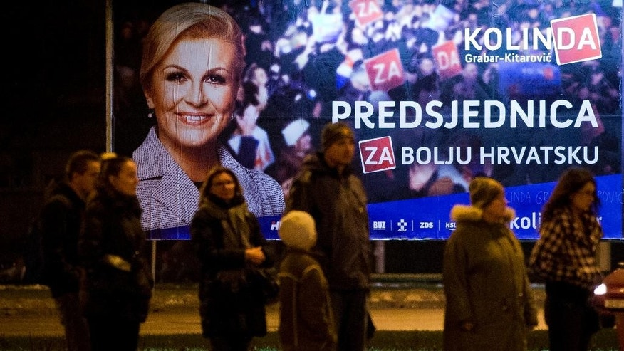 Pedestrians stand in front of an election poster of candidate Kolinda Grabar Kitarovic, in Zagreb, Croatia, Friday, Jan. 9, 2015. A liberal incumbent and a conservative rival are heading into a surprisingly close showdown in Croatia's presidential runoff held amid deep discontent over economic woes in the European Union's newest member. (AP Photo/Darko Bandic)