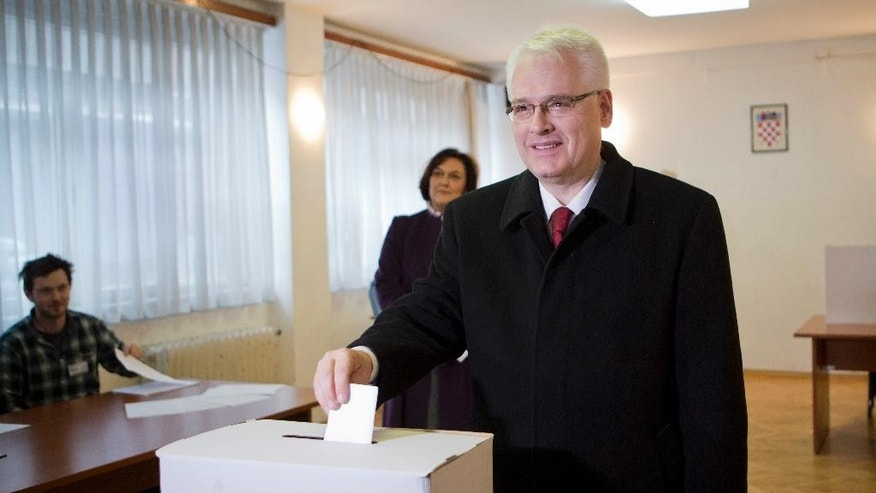 FILE - In this Sunday, Dec. 28, 2014 file photo, president incumbent Ivo Josipovic casts his ballot during the first round of presidential elections in Zagreb, Croatia. A liberal incumbent and a conservative rival are heading into a surprisingly close showdown in Croatia's presidential runoff, held amid deep discontent over economic woes in the European Union's newest member. (AP Photo/Darko Bandic, File)
