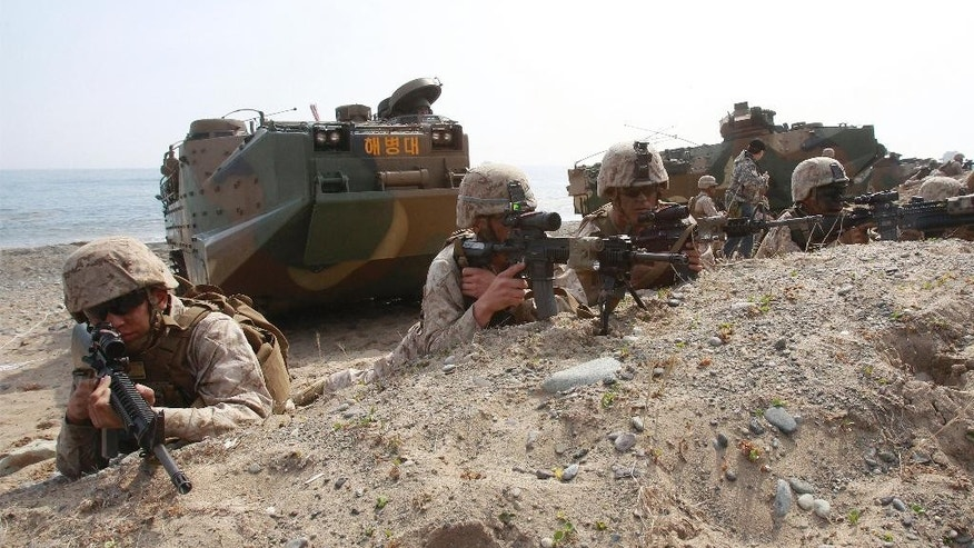 In this March 31, 2014 photo, U.S. Marines take a position during the U.S.-South Korea joint landing exercises, called Ssangyong, as part of the Foal Eagle military exercises in Pohang, South Korea. North Korea has told the United States that it's willing to impose a temporary moratorium on nuclear tests if Washington scraps planned military drills with South Korea this year, the North's official news agency said Saturday, Jan. 10, 2015. The U.S. has previously refused to cancel military drills with South Korea, even at times of high tension and has said the North must first demonstrate how serious it is about nuclear disarmament before serous talks can resume. (AP Photo/Ahn Young-joon)