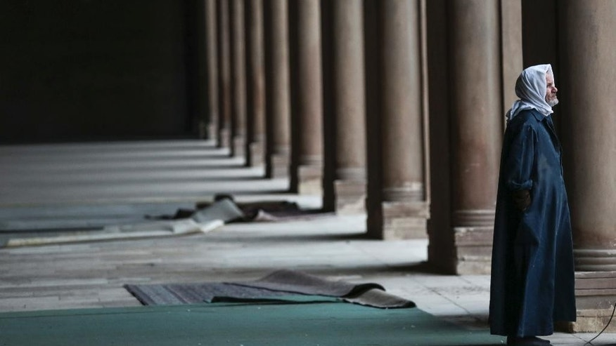 In this Friday, Jan. 9, 2015 photo, an Egyptian Muslim pauses inside Ibn-Tulun Mosque, one of the oldest mosques in Cairo, Egypt. Amid violence like the attack in Paris on a satirical newspaper over its depictions of the Prophet Muhammad, there's been increasing discussions among Muslims who say their community must re-examine their faith to modernize its interpretations and sideline extremists. There is a growing debate within Islam about whether and how to reject a radical minority that some fear is dragging them into conflict and wrecking the faith. (AP Photo/Mosa'ab Ehsamy)