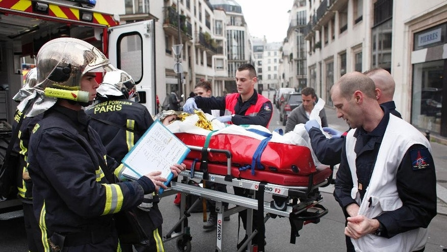 FILE - In this Wednesday, Jan. 7, 2015 file photo, an injured person is carried into an ambulance after a shooting, at the French satirical newspaper Charlie Hebdo's office, in Paris, France. Amid violence like the attack in Paris on a satirical newspaper over its depictions of the Prophet Muhammad, there's been increasing discussions among Muslims who say their community must re-examine their faith to modernize its interpretations and sideline extremists. There is a growing debate within Islam about whether and how to reject a radical minority that some fear is dragging them into conflict and wrecking the faith. (AP Photo/Thibault Camus, File)