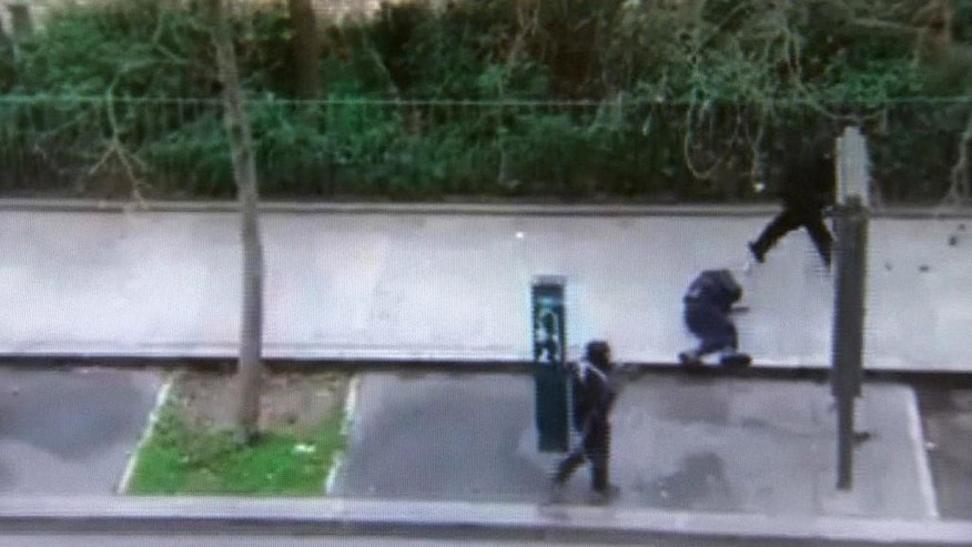 FILE - In this image made from amateur video recorded on Wednesday, Jan. 7, 2015, file photo by Jordi Mir, masked gunman walk past a police officer moments after shooting him at blank range outside the offices of French satirical newspaper Charlie Hebdo in Paris. Though it is impossible to gauge in any tangible way the effect the deadly attack on a Paris newspaper will have on recruitment by extremist groups - and there is no evidence so far that it is mobilizing large numbers of would-be jihadis - experts believe the perceived professionalism of the brothers' assault and their subsequent showdown with police could rally more supporters to militant ranks. (AP Photo/Jordi Mir, File) NO SALES