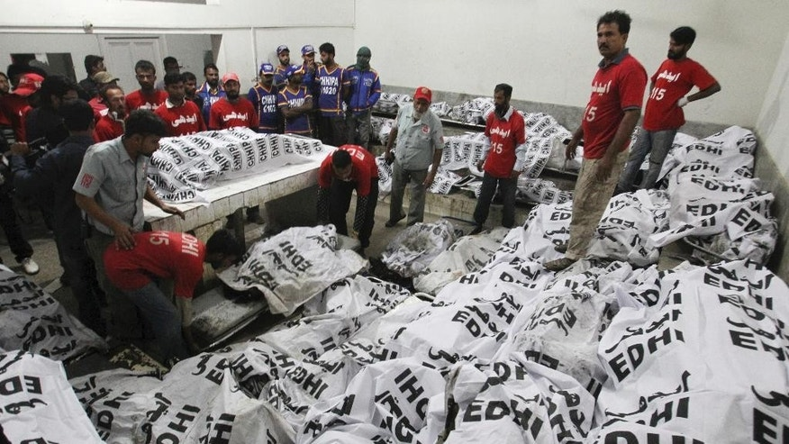 Pakistani rescue workers gather around the bodies of bus accident victims in a hospital in Karachi, Pakistan, early Sunday, Jan. 11, 2015. Dozens of people were killed when a passenger bus collided with an oil tanker on a highway near Karachi. (AP Photo/Fareed Khan)