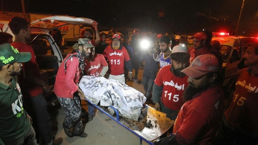 Pakistani rescue workers carry the lifeless body of a bus accident victim to a hospital in Karachi, Pakistan, early Sunday, Jan. 11, 2015. Dozens of people were killed when a passenger bus collided with an oil tanker on a highway near Karachi. (AP Photo/Fareed Khan)