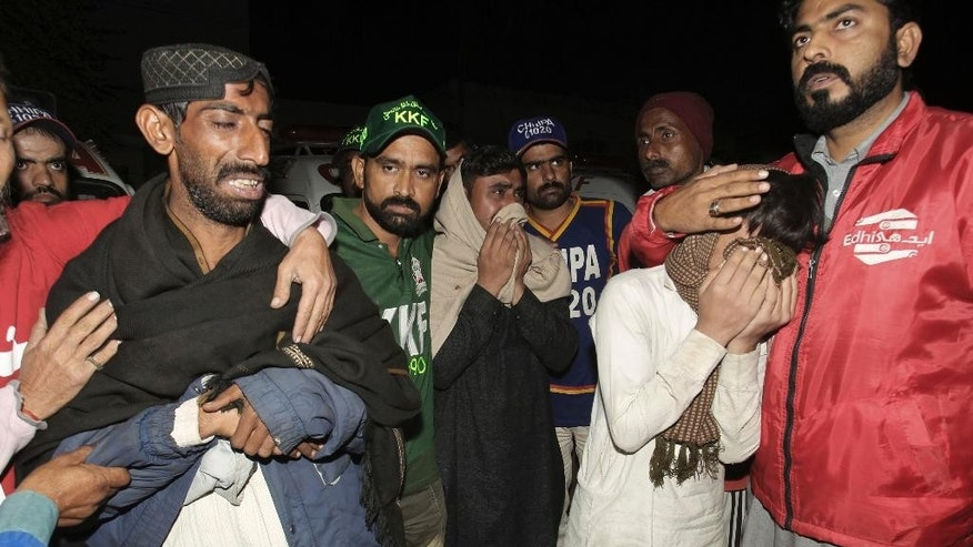 Pakistani relatives of bus accident victims mourn their death outside a hospital in Karachi, Pakistan, early Sunday, Jan. 11, 2015. Dozens of people were killed when a passenger bus collided with an oil tanker on a highway near Karachi. (AP Photo/Fareed Khan)