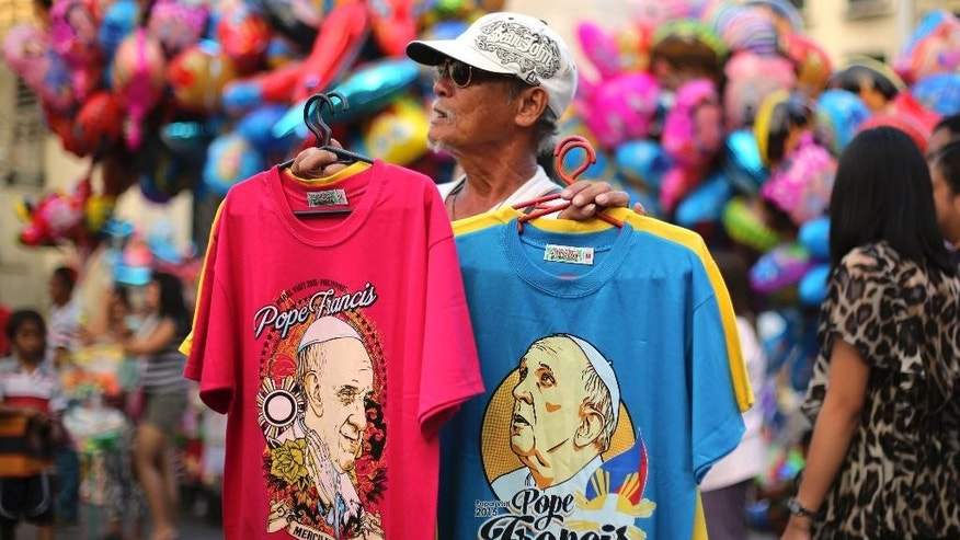 FILE - In this Jan. 4, 2015 file photo, a Filipino man sells shirts with images of Pope Francis for 150 pesos each ($3) outside a church in downtown Manila, Philippines, Sunday, Jan. 4, 2015. Pope Francis embarks on his second Asian pilgrimage on Jan. 13, 2015, visiting Sri Lanka and the Philippines exactly 20 years after St. John Paul II's record-making visit to two countries with wildly disparate Catholic populations.(AP Photo/Aaron Favila, File)