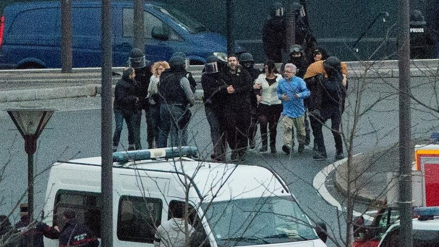 Security officers escort released hostages after they stormed a kosher market to end a hostage situation, Paris, Friday, Jan. 9, 2015. Explosions and gunshots were heard as police forces stormed a kosher grocery in Paris where a gunman was holding at least five people hostage. (AP Photo/Michel Euler)