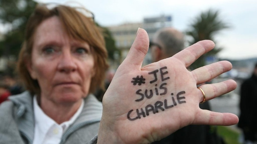 "A man holds a candle and a sticker reading "" I am Charlie"", during a demonstration in Paris, Wednesday, Jan. 7, 2015. Three masked gunmen shouting ""Allahu akbar!"" stormed the Paris offices of a satirical newspaper, Charlie Hebdo, Wednesday, killing 12 people, including its editor, before escaping in a car. It was France's deadliest postwar terrorist attack. (AP Photo/Christophe Ena)"