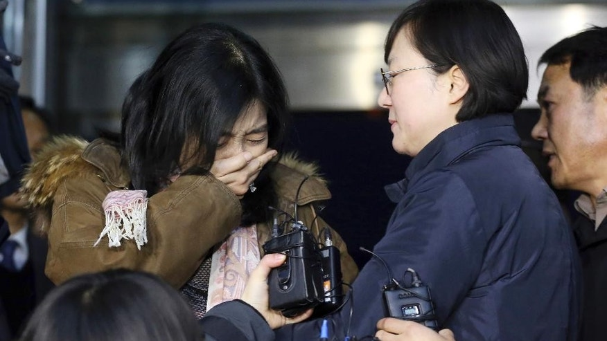 A Korean-American Shin Eun-mi, left, weeps  as she arrives to leave for the United Sates at the Incheon International Airport in Incheon, South Korea, Saturday, Jan. 10, 2015. Shin accused of praising rival North Korea in a recent lecture said she is being deported Saturday from South Korea, in the latest in a series of cases that critics say infringe on the country's freedom of speech. (AP Photo/Yonhap, Shin Joon-hee)  KOREA OUT