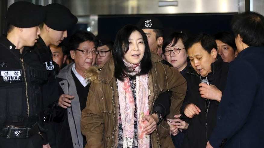 A Korean-American Shin Eun-mi, center, arrives at the Incheon International Airport for departure in Incheon, South Korea, Saturday, Jan. 10, 2015. Shin accused of praising rival North Korea in a recent lecture said she is being deported Saturday from South Korea, in the latest in a series of cases that critics say infringe on the country's freedom of speech. (AP Photo/Yonhap, Shin Joon-hee)  KOREA OUT