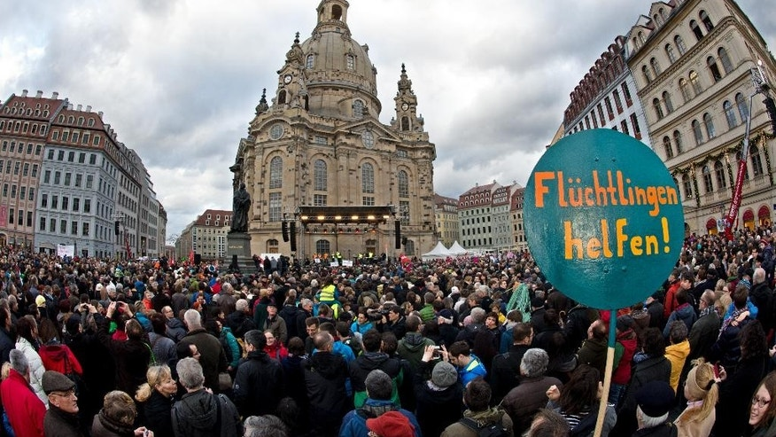 Tens of thousands participate in a demonstration against  racism  and for an open society   in Dresden, eastern Germany, Saturday Jan. 10, 2015. .The protests Saturday came in reaction to weekly anti-Islamic demonstrations that have been taking place for months in Dresden. The weekly rallies are organized by a group calling itself Patriotic Europeans against the Islamization of the West, or PEGIDA. Those rallies have been attended by up to 18,000 people, but Saturday's counter protests mobilized more than twice the crowds  around 35,000 protesters. Sign reads : Help Refugees.  (AP Photo/dpa, Arno Burgi)