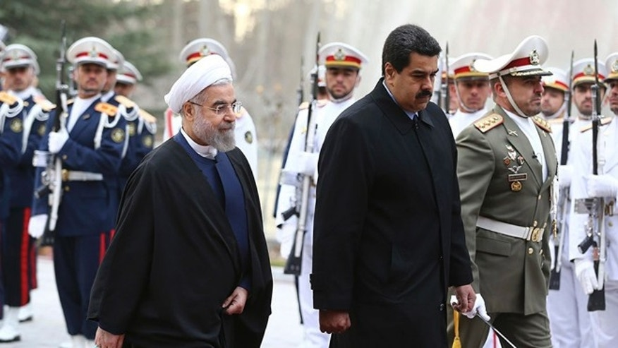 In this photo released by the official website of the office of the Iranian Presidency, Venezuelan President Nicolas Maduro, center, is welcomed by his Iranian counterpart Hassan Rouhani, left, during his official arrival ceremony at the Saadabad Palace in Tehran, Iran, Saturday, Jan. 10, 2015.  (AP Photo/Iranian Presidency Office, Mohammad Berno)