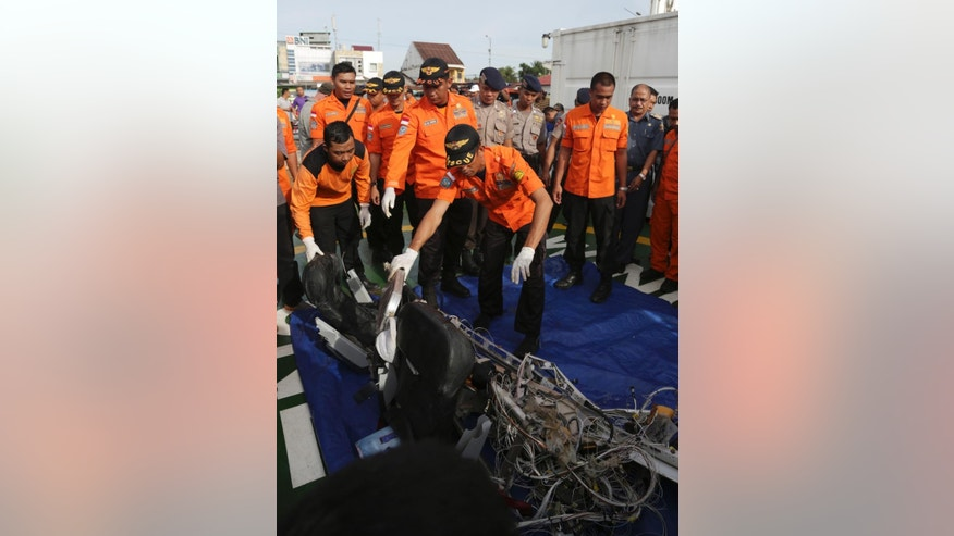 Members of National Search And Rescue Agency look at the airplane parts found floating in the water near the site where AirAsia Flight 8501 disappeared at Kumai port in Pangkalan Bun, Sunday, Jan. 11, 2015. A tail section from the AirAsia plane that crashed into the Java Sea late last month, killing all 162 people on board, became the first major wreckage lifted off the ocean floor Saturday, Jan. 10, but the all-important black boxes were not found inside. (AP Photo/Achmad Ibrahim)