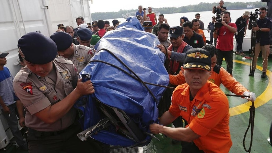 Members of National Search And Rescue Agency carry the airplane parts found floating in the water near the site where AirAsia Flight 8501 disappeared at Kumai port in Pangkalan Bun, Sunday, Jan. 11, 2015. A tail section from the AirAsia plane that crashed into the Java Sea late last month, killing all 162 people on board, became the first major wreckage lifted off the ocean floor Saturday, Jan. 10, but the all-important black boxes were not found inside. (AP Photo/Achmad Ibrahim)