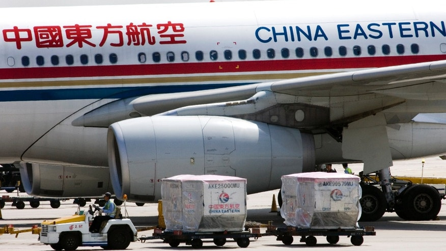Aug. 29, 2007: A carter drives past a China Eastern airliner parked at the Beijing International Airport in Beijing, China.