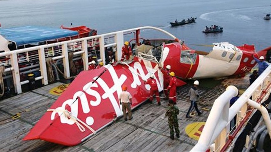 Jan.11, 2015.Crew members of Crest Onyx ship prepare to unload parts of AirAsia Flight 8501 from a ship at Kumai port in Pangkalan Bun.