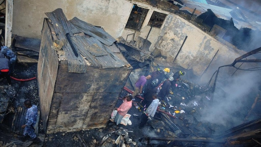 "Firemen walk through wreckage at the Taitu Hotel following a fire at the historical landmark built in 1907, in the capital Addis Ababa, Ethiopia Sunday, Jan. 11, 2015.  A fire department official says the fire has damaged the hotel which featured the city's famous jazz club ""Jazz Amba"", now destroyed, which was frequented by foreigners and locals alike. (AP Photo/Elias Asmare)"