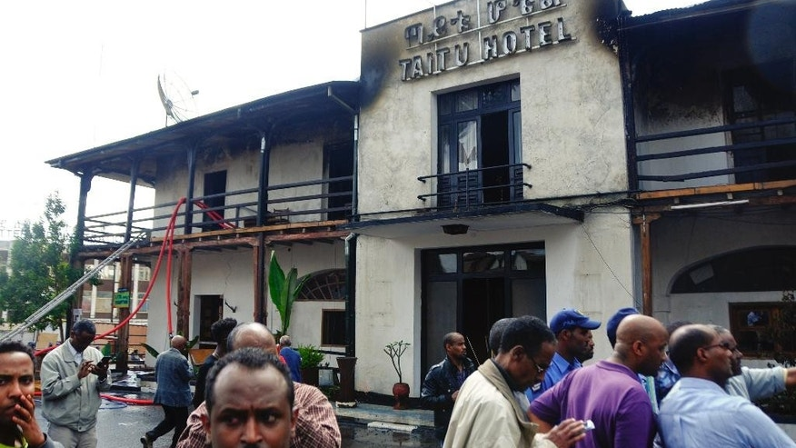 "Onlookers gather outside the Taitu Hotel following a fire at the historical landmark built in 1907, in the capital Addis Ababa, Ethiopia Sunday, Jan. 11, 2015. A fire department official says the fire has damaged the hotel which featured the city's famous jazz club ""Jazz Amba"", now destroyed, which was frequented by foreigners and locals alike. (AP Photo/Elias Asmare)"