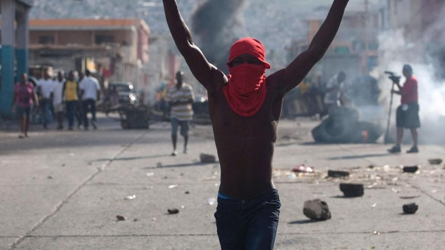 A masked protester gestures during a protest demanding the resignation of President Michel Martelly in Port-au-Prince, Haiti, Sunday, Jan. 11, 2015. At the same time, Martelly and opposition officials were locked again in negotiations at a hotel, trying to forge a last-minute deal to resolve a standoff stalling elections. Martelly will rule by decree if they don't resolve the political crisis by the end of Monday. (AP Photo/Dieu Nalio Chery)