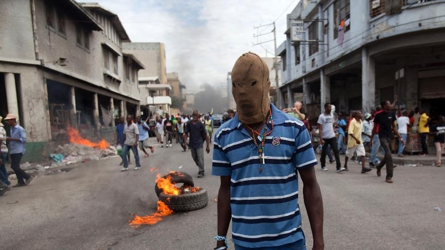 A masked protester walks in the street where burning tires were set up by protesters demanding the resignation of President Michel Martelly in Port-au-Prince, Haiti, Sunday, Jan. 11, 2015. At the same time, Martelly and opposition officials were locked again in negotiations at a hotel, trying to forge a last-minute deal to resolve a standoff stalling elections. Martelly will rule by decree if they don't resolve the political crisis by the end of Monday. (AP Photo/Dieu Nalio Chery)