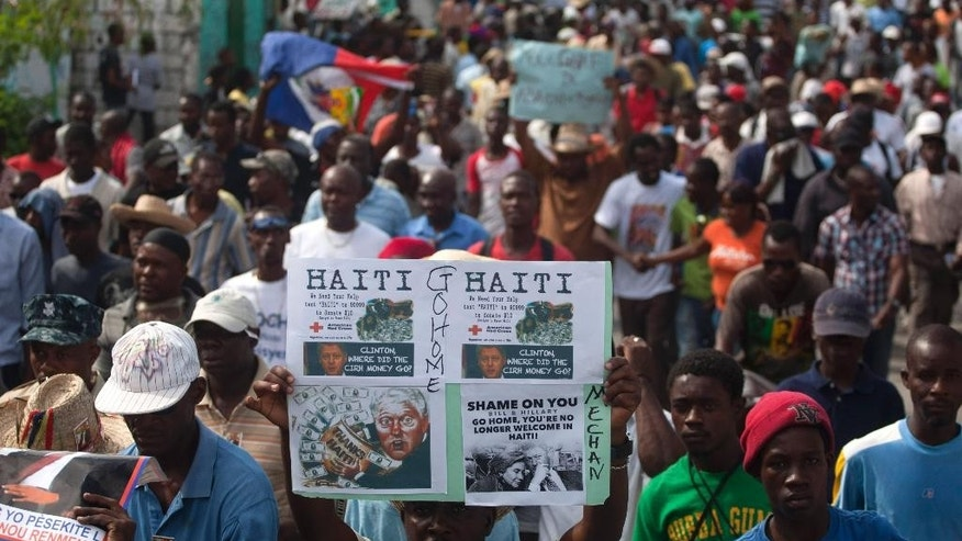 A demonstrator holds up a sign showing images of former President Bill Clinton that asks where the aid money for reconstruction went during a protest demanding the resignation of President Michel Martelly in Port-au-Prince, Haiti, Sunday, Jan. 11, 2015. At the same time, Martelly and opposition officials were locked again in negotiations at a hotel, trying to forge a last-minute deal to resolve a standoff stalling elections. Martelly will rule by decree if they don't resolve the political crisis by the end of Monday. (AP Photo/Dieu Nalio Chery)