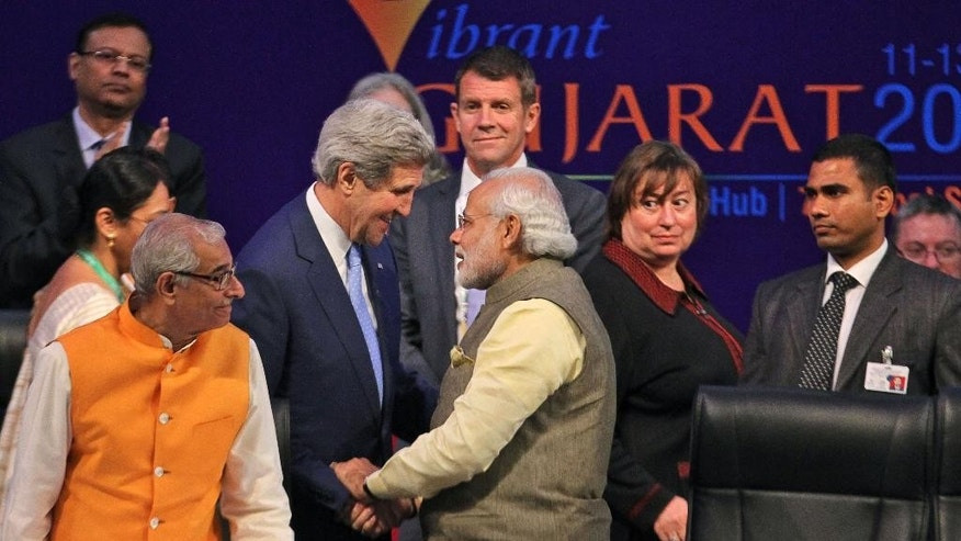 Indian Prime Minister Narendra Modi, center, speaks with U.S. Secretary of State John Kerry, second from left, at the Vibrant Gujarat summit in Gandhinagar, India, Sunday, Jan. 11, 2015. Kerry is in India to attend an international investment conference and push trade ties with the giant South Asian nation ahead of visit by President Barack Obama later this month. (AP Photo/Ajit Solanki)