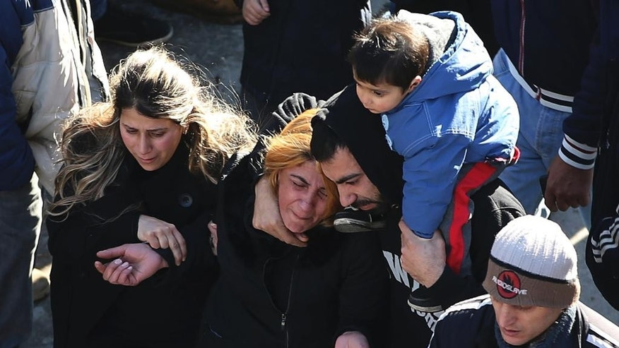 An Alawite woman, center, mourns over the death of her relative who was killed at a coffee shop where a suicide bombing struck it Saturday night, during their funeral procession in a predominantly Alawite neighborhood of the northern port city of Tripoli, Lebanon, Sunday, Jan. 11, 2015. Syria's al-Qaida-linked Nusra Front claimed responsibility on Twitter for the blast that killed several people and wounded more than 30 in Tripoli's neighborhood of Jabal Mohsen, saying it was a twin suicide attack. (AP Photo/Hussein Malla)