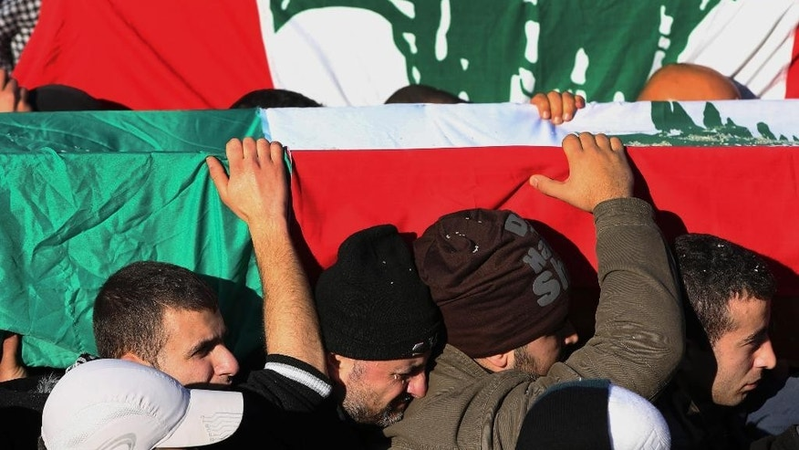 Alawite mourners carry coffins wrapped by Lebanese flags of those who were killed at a coffee shop where a suicide bombing struck it Saturday night, during their funeral procession in a predominantly Alawite neighborhood of the northern port city of Tripoli, Lebanon, Sunday, Jan. 11, 2015. Syria's al-Qaida-linked Nusra Front claimed responsibility on Twitter for the blast that killed several people and wounded more than 30 in Tripoli's neighborhood of Jabal Mohsen, saying it was a twin suicide attack. (AP Photo/Hussein Malla)