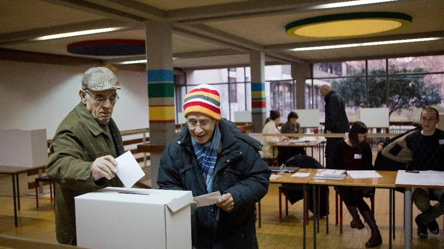 Voters cast their ballots at a polling station in Zagreb, Croatia, Sunday, Jan. 11, 2015. A liberal incumbent and a conservative rival are heading into a surprisingly close showdown in Croatia's presidential runoff held amid deep discontent over economic woes in the European Union's newest member. (AP Photo/Darko Bandic)