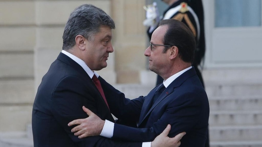 French President Francois Hollande welcomes Ukrainian President Petro Poroshenko, left, at the Elysee Palace, Paris, Sunday, Jan. 11, 2015. A rally of defiance and sorrow, protected by an unparalleled level of security, on Sunday will honor the 17 victims of three days of bloodshed in Paris that left France on alert for more violence. (AP Photo/Thibault Camus)