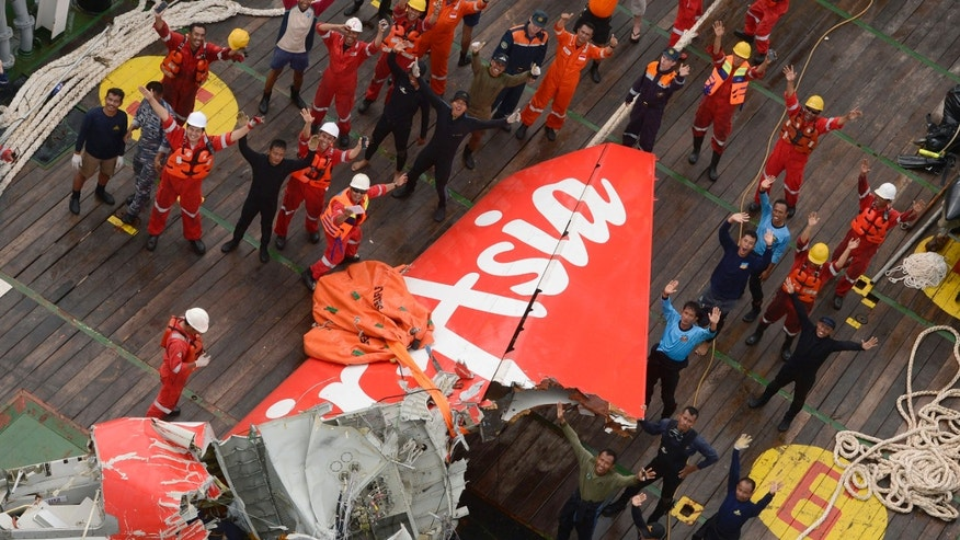 Jan. 10, 2015: Rescuers wave at an Indonesian Air Force helicopter near portion of AirAsia Flight 8501 after it was recovered from the sea floor on the deck of a rescue ship on the Java Sea
