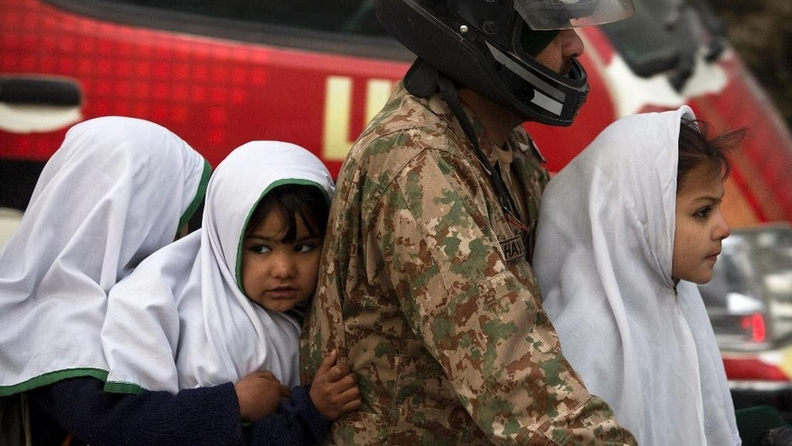 A Pakistan army soldier transport his children to a school near the Army Public School targeted by Taliban militants, in Peshawar, Pakistan, Monday, Jan. 12, 2015. Pakistani children and their parents returned Monday to the school where Taliban gunmen killed 150 of their classmates and teachers. (AP Photo/B.K. Bangash)