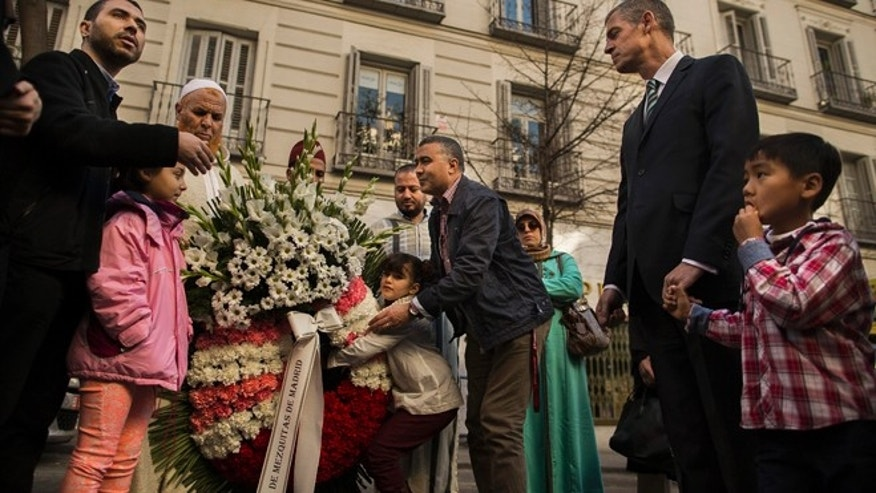 Jan. 11, 2015: Members of the Islamic community of Madrid, center offers a funeral wreath to the French Ambassador to Spain, Jerome Bonnafont, second right, in support of the victims who were shot by terrorists at the Charlie Hebdo satirical journal and the kosher storey in Paris last week, as they meet outside of the French Embassy of Madrid, Spain.