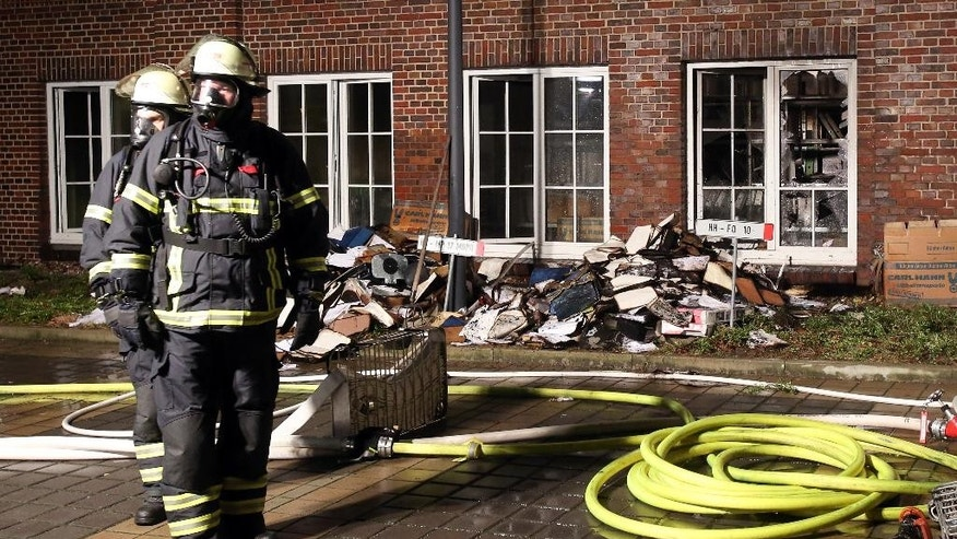 Firefighters stand outside the building of the 'Hamburger Morgenpost' in Hamburg, northern Germany, Sunday morning, Jan. 11, 2015. According to police fire broke out in an archive room of the paper after an arson attack. The newspaper ran caricatures of the Charlie Hebdo newspaper after the attack on Wednesday. (AP Photo/dpa, Bodo Marks)