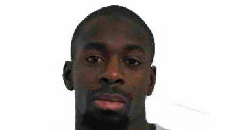 CORRECTS FIRST NAME OF FEMALE SUSPECT This photo provided by the Paris Police Prefecture Friday, Jan. 9, 2015 shows Amedy Coulibaly A suspect in the kosher market attack. A police official says the man who has taken at least five people hostage in a kosher market on the eastern edges of Paris Friday appears linked to the newsroom massacre earlier this week that left 12 people dead.  Paris police released a photo of Amedy Coulibaly as a suspect in the killing Thursday of a policewoman, and the official named him as the man holed up in the market. He said the man is armed with an automatic rifle and some hostages have been gravely wounded. He said a second suspect, a woman named Hayat Boumddiene, is the gunman's accomplice. (AP Photo/Prefecture de Police de Paris)