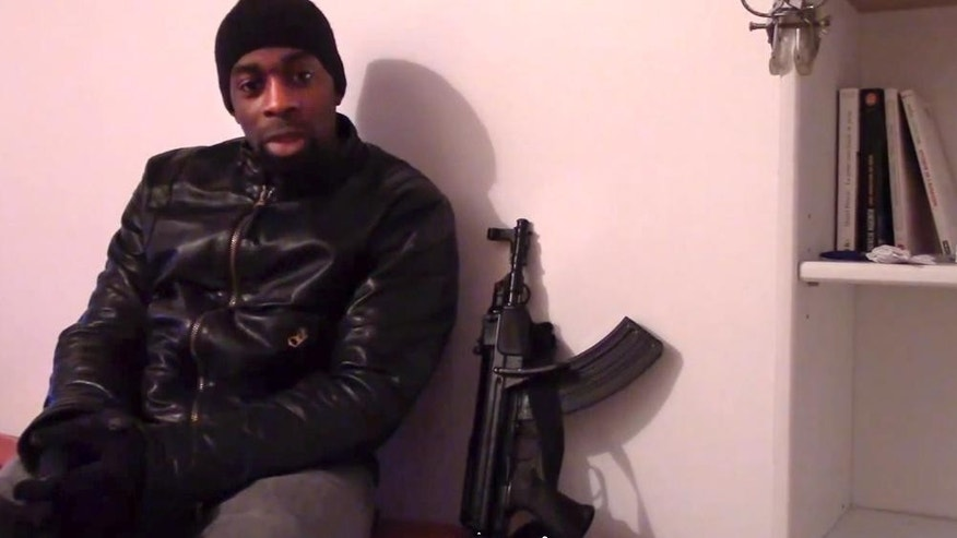 "AP PROVIDES ACCESS TO THIS HANDOUT PHOTO TO BE USED SOLELY TO ILLUSTRATE NEWS REPORTING OR COMMENTARY ON THE FACTS OR EVENTS DEPICTED IN THIS IMAGE - This image made from a video posted online by militants on Sunday, Jan. 11, 2015, shows slain hostage-taker Amedy Coulibaly, who shot a policewoman and four hostages at a kosher grocery, with a gun as he defends the Paris attacks carried out on the satirical newspaper, police and a Jewish store. At one point in the video, Coulibaly says Charlie Hebdo will be attacked ""tomorrow"" and that he and the (Said and Cherif Kouachi) brothers were coordinating. Speaking in broken Arabic, he gives his allegiance to the head of the Islamic State. (AP Photo/Militant Video)"