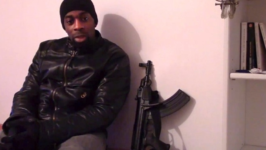 "This image made from a video posted online by militants on Sunday, Jan. 11, 2015, shows slain hostage-taker Amedy Coulibaly, who shot a policewoman and four hostages at a kosher grocery, with a gun as he defends the Paris attacks carried out on the satirical newspaper, police and a Jewish store. At one point in the video, Coulibaly says Charlie Hebdo will be attacked ""tomorrow"" and that he and the (Said and Cherif Kouachi) brothers were coordinating. Speaking in broken Arabic, he gives his allegiance to the head of the Islamic State."