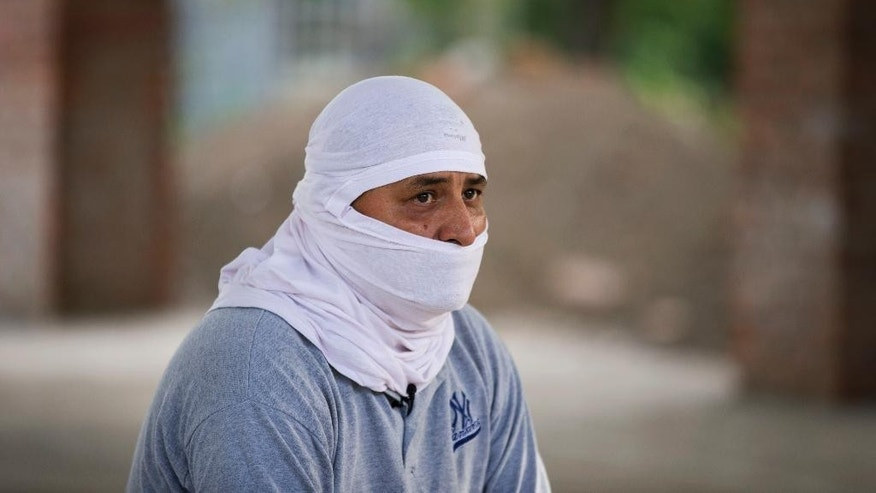 CORRESTS LAST NAME TO VAZQUEZ -In this Thursday, Jan. 8, 2015 photo, Carlos Vazquez, a vigilante and survivor of a recent shooting, describes the confrontation between the vigilante group and government forces in an interview at a community center in Colonias, outside Apatzingan, Michoacan, Mexico. He covered his face out of fear of recriminations by federal police and introduced himself as Carlos Vasquez. He said he was in a civilian convoy following the federal police during a shooting that left nine civilians dead during federal operations in the community of Apatzingan Tuesday, Jan. 6, 2015. (AP Photo/Rebecca Blackwell)
